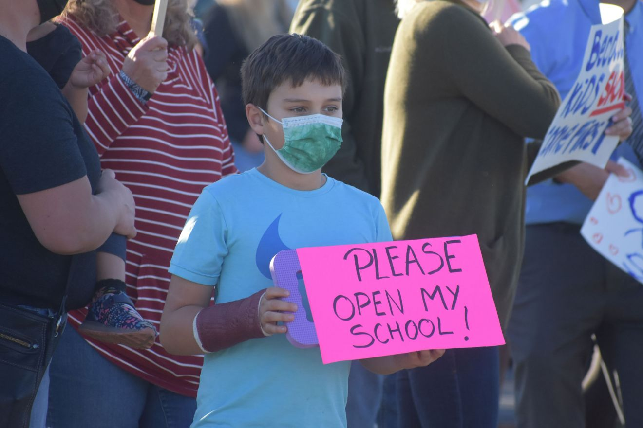 A student holds a sign urging trustees of the Orcutt Union School District to return to in-person as soon as possible.