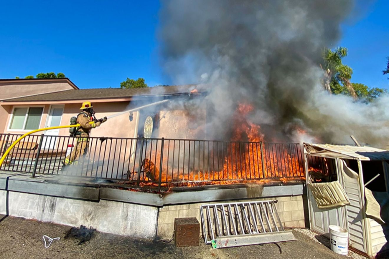 A Santa Barbara County firefighter hoses down a deck on fire at a home on Cieneguitas Road Thursday afternoon.