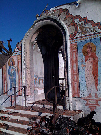 Mount Calvary Retreat House's welcoming entrance arch stands in ruin, its murals spattered by wind-hurled embers.