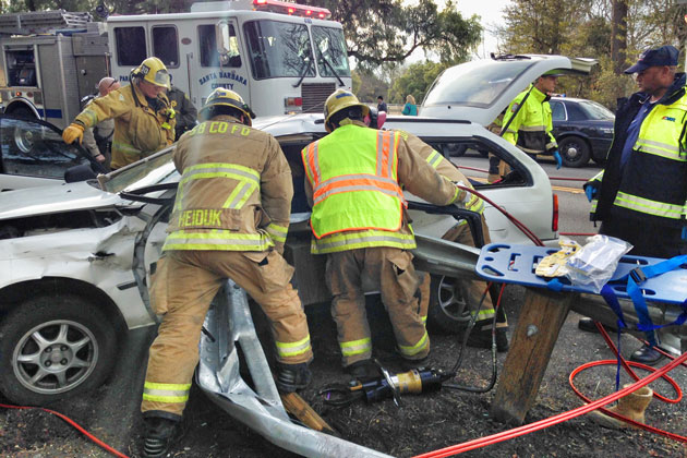 Firefighters work to extricate two people from the wreckage of a single-car crash Sunday on Highway 154 near Los Olivos. Four people were injured, including one who was airlifted to Santa Barbara Cottage Hospital.