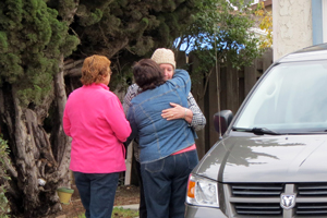 Neighbors comfort one of the residents of a Chaparral Street house badly damaged in a Sunday afternoon fire. (Gina Potthoff / Noozhawk photo)