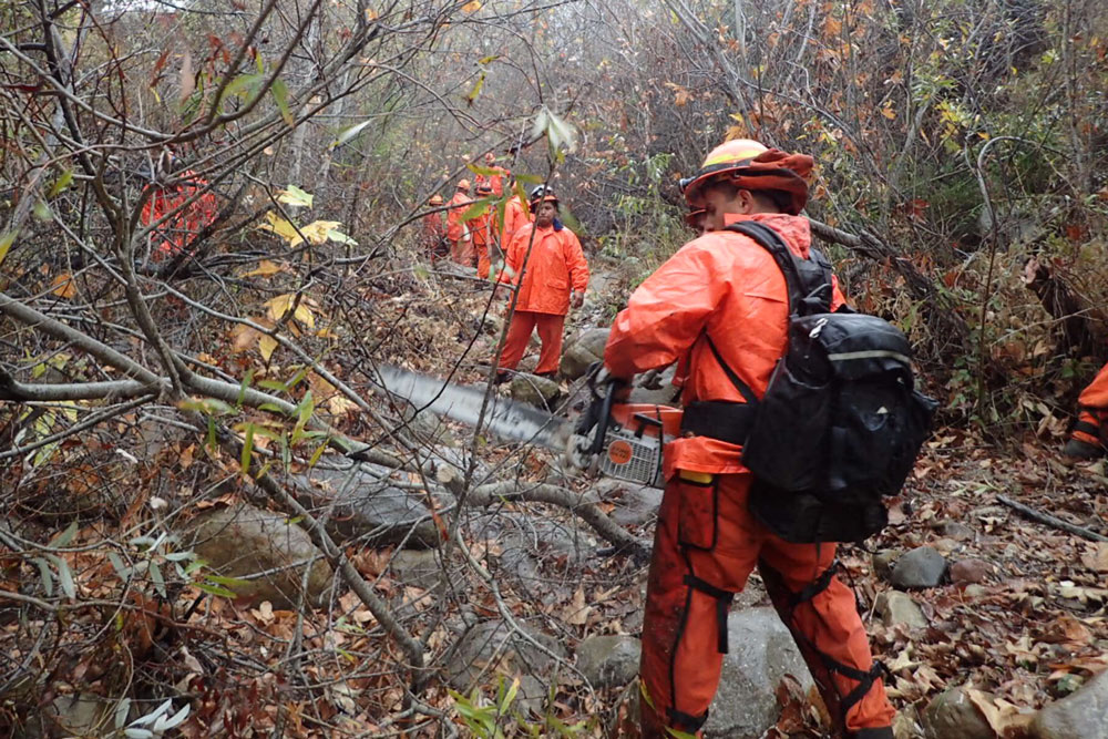 With rain falling, a CalFire inmate crew from San Luis Obispo cuts and clears potentially run off clogging debris from Toro Canyon Creek in Carpinteria on Monday. Heavy rain is expected for the area overnight.
