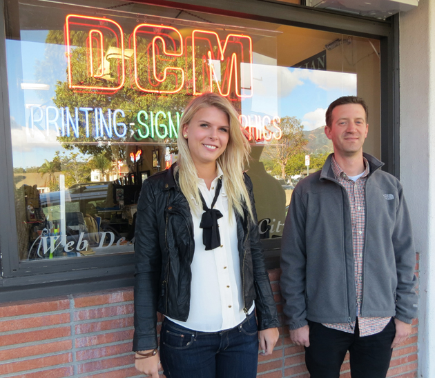 <p>DCM Graphics intern Eleanor Lofgren, left, and lead designer Josh Gorfine stand in front of the company&#8217;s renovated, smaller new store at 16B W. Calle Laureles in Santa Barbara.</p>