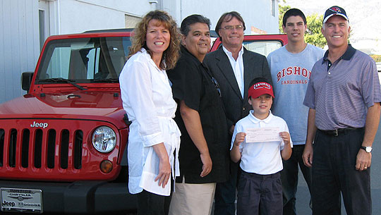From left, new Jeep owners Alison and Gregg Nevarez, Santa Barbara Chrysler Jeep owner Jim Crook, Daniel and Andy Nevarez, and Bishop Diego High's Cardinal Club president Jim Slaught.
