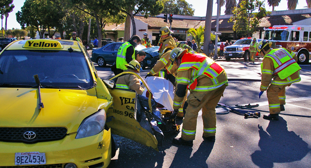 Emergency crews tend to a driver who was injured Friday in a two-vehicle accident at Haley and Santa Barbara streets in downtown Santa Barbara. (Tom Bolton / Noozhawk photo)
