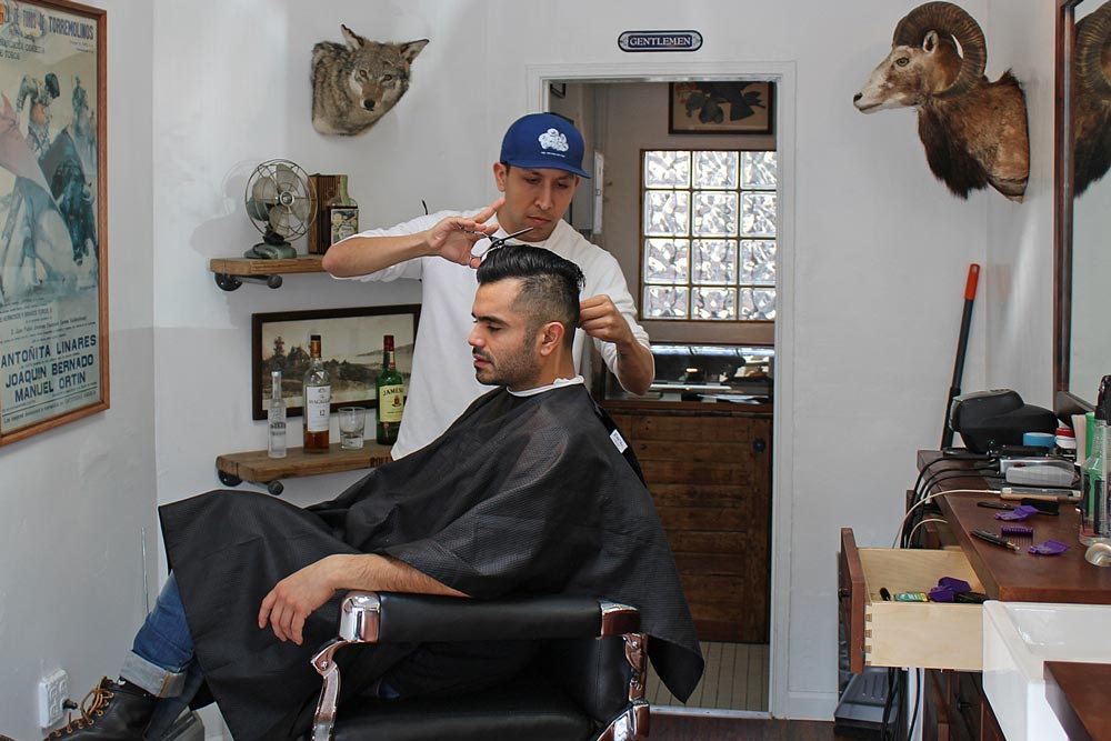 Isaac Alvarado gives a haircut in the 200-square-foot Wolf's Head Annex barber shop.