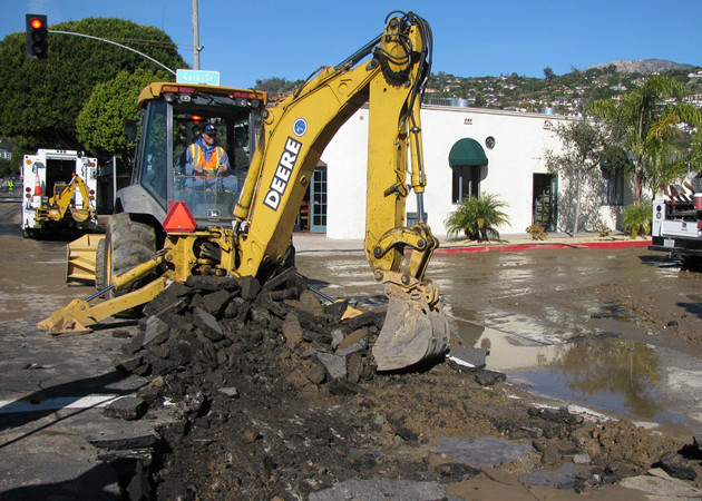 A backhoe breaks up the pavement at Milpas and Cota streets on Santa Barbara's Eastside Monday to reach a broken water main. (Giana Magnoli / Noozhawk photo)