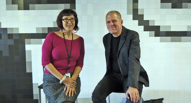 Lynda Weinman and Bruce Heavin, co-founders of lynda.com, sit beneath a depiction of their company's logo at their offices in Carpinteria. The company this week received a $103 million venture-capital investment. (Gina Potthoff / Noozhawk photo)