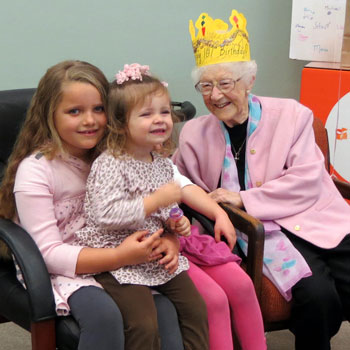 Edythe Kirchmaier sits with her great-grandchildren earlier this year during a reception celebrating her 107th birthday at Direct Relief headquarters in Goleta. She died Saturday at age 107. (Gina Potthoff / Noozhawk file photo)