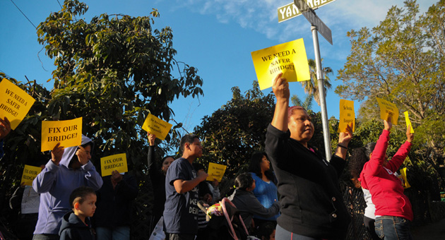<p>Maria Delgado and other Eastside residents hold up signs Wednesday encouraging the City of Santa Barbara to fix the bridge at Montecito and Yanonali streets.</p>