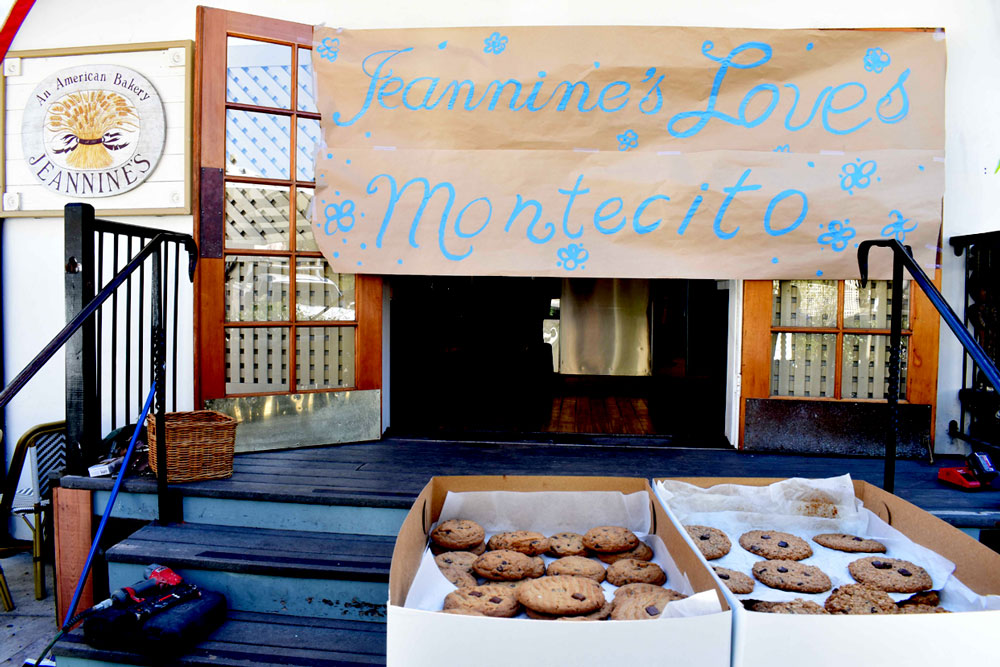 Fresh-baked cookies are offered outside Jeannine's American Bakery on Coast Village Road, as businesses prepare to welcome back customers after weeks of closures due to fire and floods. An evacuation warning for the area was lifted at noon on Tuesday