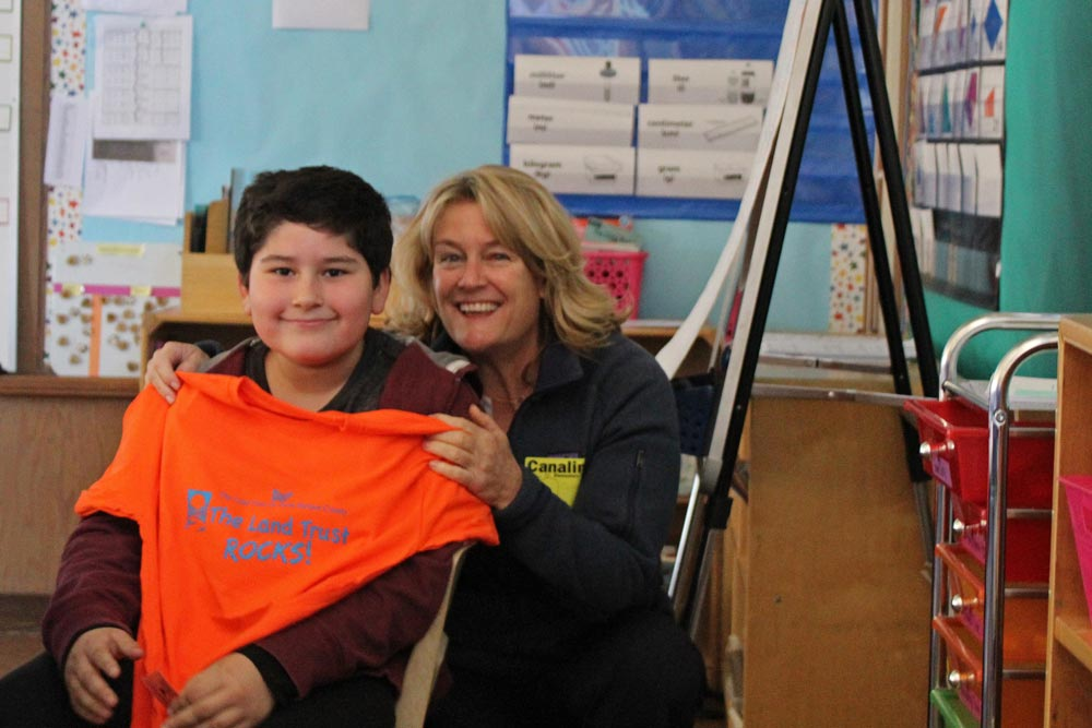Carrie Mullen of the Land Trust for Santa Barbara County presents Canalino Elementary School student Yohann Garcia a shirt in thanks for students' efforts to fundraise toward purchasing more Carpinteria Bluffs land.