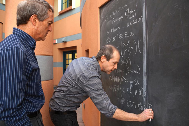 <p>Kavli Institute for Theoretical Physics scholar Peter Orland shows KITP&#8217;s Joe Polchinski a solution to a physics problem.</p>