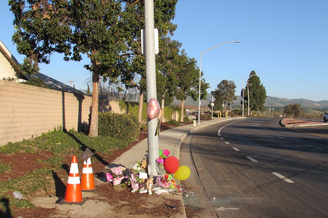 Dirt and broken glass make for a stark contrast with balloons, flowers and candles paying tribute to Breanna Rodriguez.