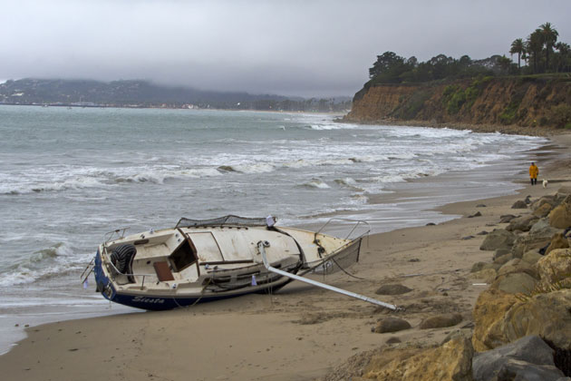 The wreckage of a sailboat that broke free of its mooring remains on Butterfly Beach in Montecito Sunday as the latest storm was bringing rain, wind and high surf to the region.
