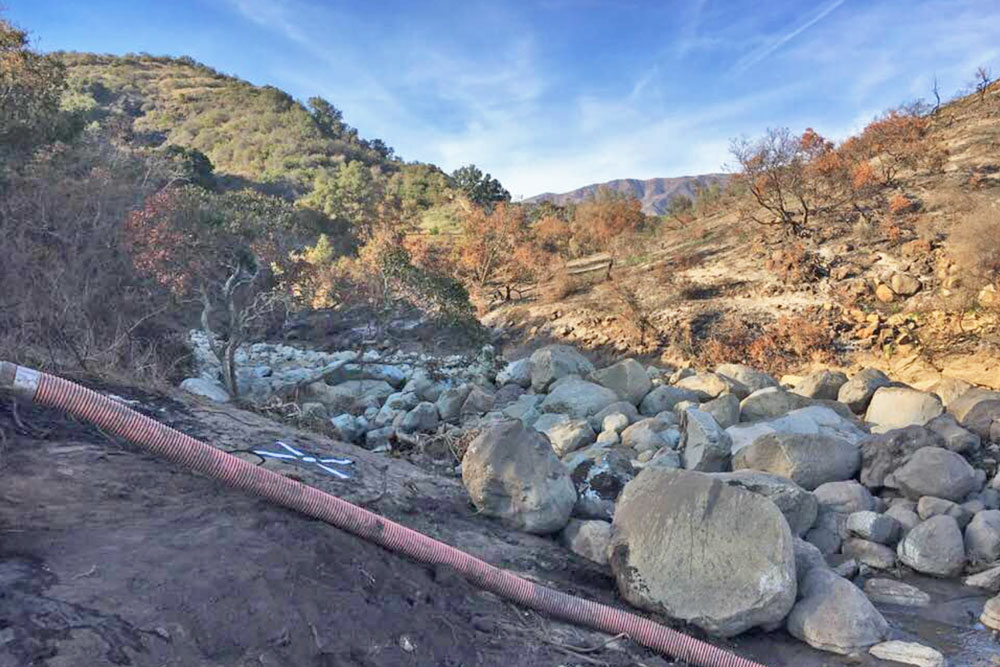 Earlier this month, above, the Santa Monica Debris Basin in Carpinteria still held a large quantity of boulders and other materials brought down from the Thomas Fire burn area for a strong storm on Jan. 9. County officials hope to have it completely cleared by March 15.