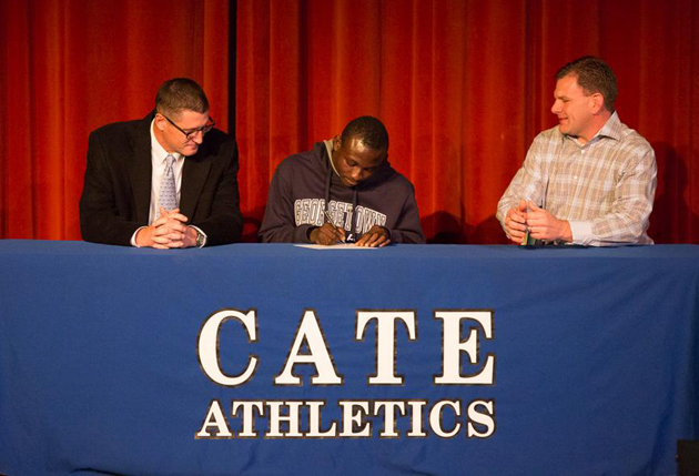 Cate School senior Joshua Yaro, center, signs a national letter of intent on Wednesday to play soccer for Georgetown University. Joining Yaro are Cate varsity soccer coach Peter Mack, left, and assistant coach Jim Kane. (Cate School photo)