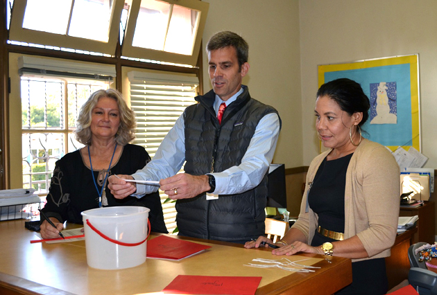 Peabody Charter School Principal Demian Barnett pulls names out of a bucket for the school's first lottery for next year's attendance, with the assistance of office coordinator Holly Christopher Munoz, left, and office assistant Maria Cruz. (Giana Magnoli / Noozhawk photo)
