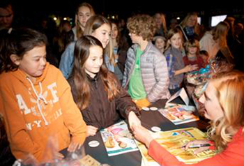 World-class surfer Lakey Peterson signs autographs for a few of her young fans at Sunday night's opening of her first feature-length film, Zero to 100