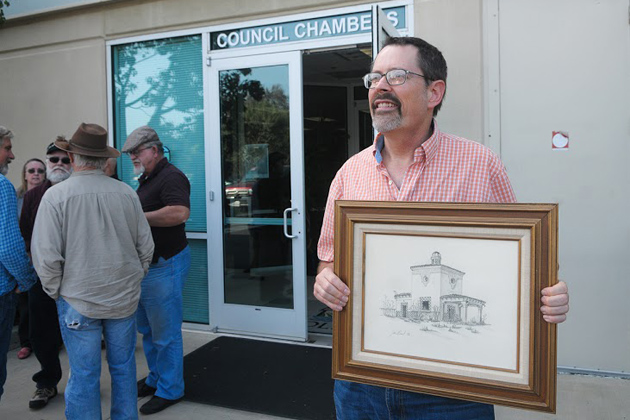 Goleta Resident John Kalstrom holds a sketch of the Barnsdall-Rio Grande Gas Station, drawn by his mother-in-law, Jan Bisol, in 1976. Kalstrom was one of several speakers who showed up Tuesday to support the gas station being designated as a historic landmark at the Goleta City Council meeting.