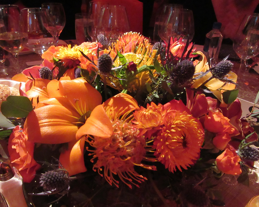 Coral and orange floral centerpieces reflected the event's festive color theme.