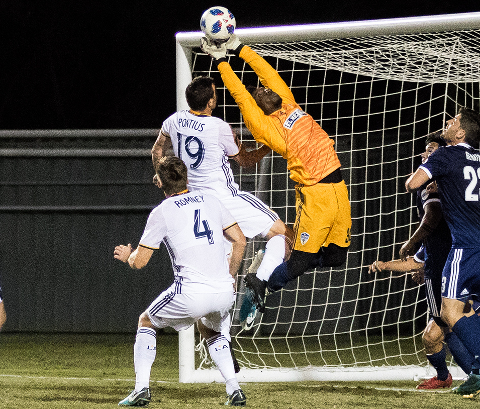 Chris Pontius of the L.A. Galaxy challenges the Fresno FC goalkeeper for a crossing ball during Thursday night's preseason soccer match at Harder Stadium.