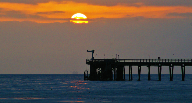 The sun sets behind an oil pier at Haskell's Beach in Goleta, where a young woman who was the first victim of sexually violent predator Tibor Karsai killed herself in 1985. Karsai may soon be released in Santa Barbara County as a transient. (Tom Bolton / Noozhawk photo)