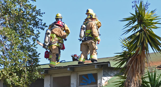 <p>Santa Barbara firefighters stand on the roof of a building on De la Vina Street on Wednesday as part of a training exercise.</p>