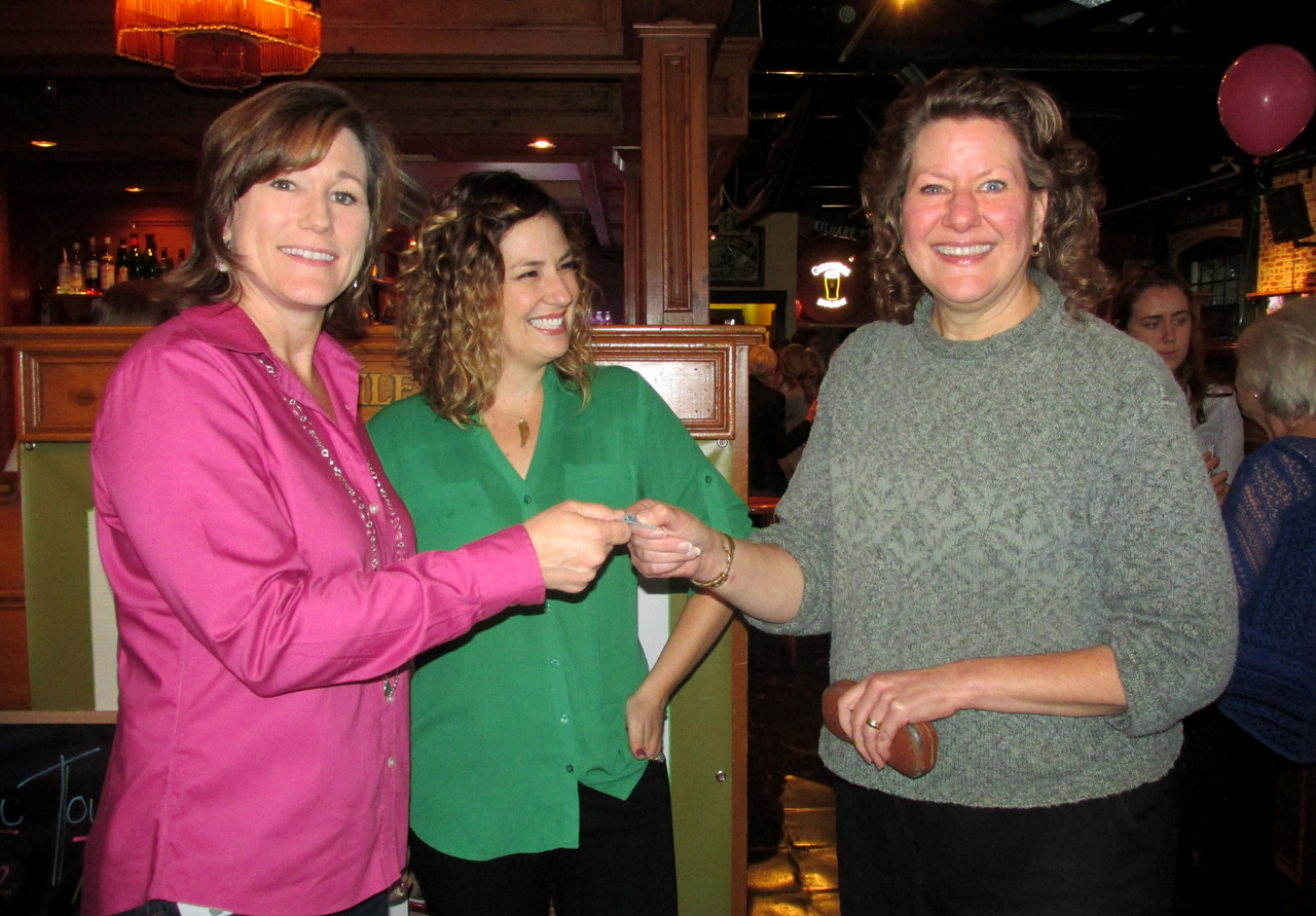 Cancer Center staff member Cami Stockero, left, and Jennie Jacobs present a raffle ticket to local attorney Sharon Kennedy.