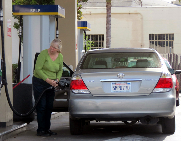 A customer fills up her vehicle's gas tank at USA Gasoline at 8 S. Milpas St. in Santa Barbara, which on Thursday offered one of the area's lowest prices of regular gasoline at $4.19 per gallon. (Gina Potthoff / Noozhawk photo)