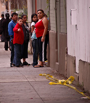 Neighbors gathered in small groups to watch the police investigation unfold near Brownie's Market on the corner of De la Vina and Haley streets.