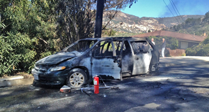 The charred remains of a minivan after a fire Monday that seriously burned a young girl. (John Palminteri / KEYT News photo)