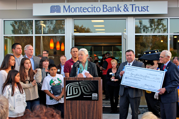 Montecito Bank & Trust President and CEO Janet Garufis, center, with help from Towbes Group founder Michael Towbes, right, and Montecito Bank & Trust branch manager Javier Quezada, presents a check for $5,000 to the Goleta Boys & Girls Club during Tuesday's grand opening celebration of the bank's new branch at 6900 Hollister Ave. in Goleta.