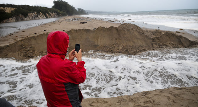 <p>A man takes a photo of water rushing out of the Goleta Slough on Friday after Santa Barbara County officials received an emergency permit to break through the sandbar in order to reduce a threat of flooding to the Santa Barbara Airport and the surrounding neighborhood.</p>
