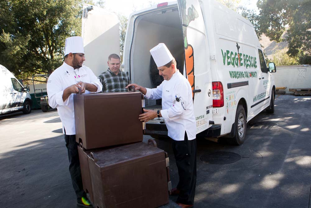 Kevin Kemp, center, a van driver for Veggie Rescue, watches Chumash Casino Resort chefs Sabino Zarate, left, and Octavio Flores prepare to load insulated containers of donated food for transport to the Buellton Senior Center.