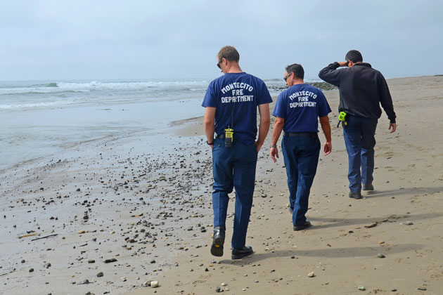 Montecito firefighters survey oil that washed up Wednesday on Miramar Beach in Montecito. Officials were still trying to determine if the globs were from natural seepage or a spill, and the investigation has been turned over to the state Office of Emergency Management.