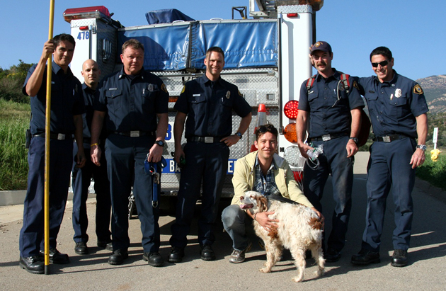 <p>Santa Barbara County firefighters pose for a photo with Biscuit, a 13-year-old Brittany spaniel rescued by the firefighters on Monday after falling into an underground drainage pipe near San Marcos Pass.</p>