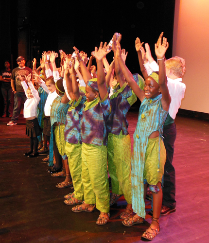 Members of the African Children's Choir raise their hands to the audience after performing last Friday at UCSB's Campbell Hall as part of the Arts & Lectures Winter Festival.