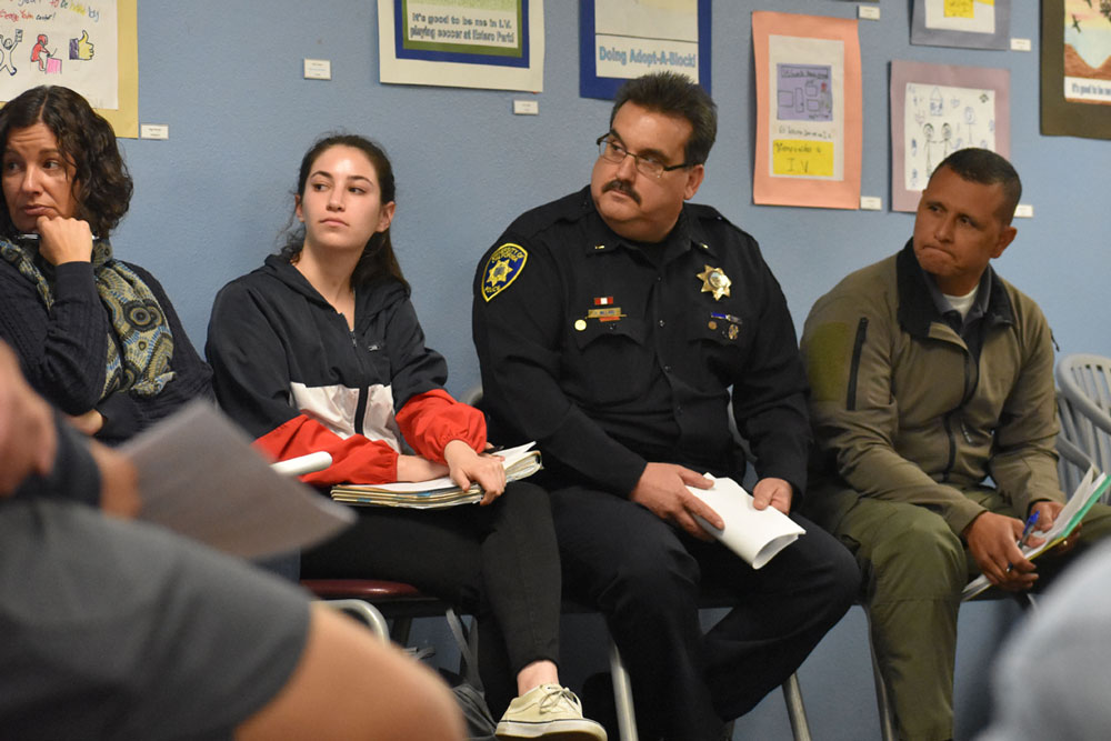 Lt. Juan Camarena, right, who oversees the Isla Vista Foot Patrol station, attends a town hall meeting Tuesday in Isla Vista, discussing plans for Deltopia with area residents and community members.