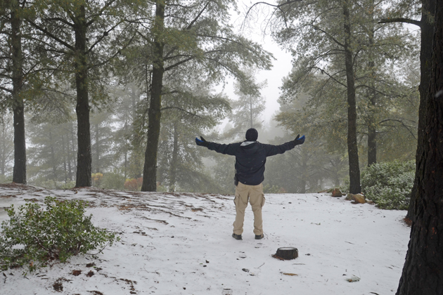 Michael Lopez enjoys the rare snow after cold, wet weather in the La Cumbre Peak area Monday morning.