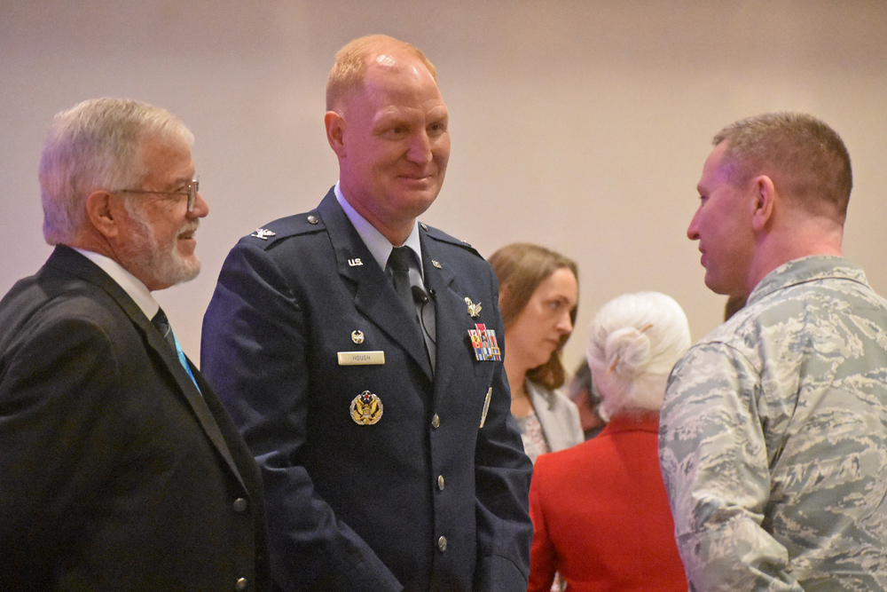 Col. Michael Hough, center, 30th Space Wing commander, talks talks to Orcutt resident and event master of ceremonies Bob Hatch, left, and an airman.