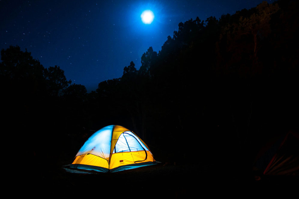 Camping on serene night beneath light of moon.