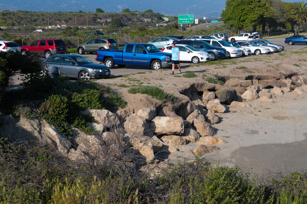 Cars sit in a parking lot at Goleta Beach Park near a rock revetment that was installed to keep erosion of the beach at bay.
