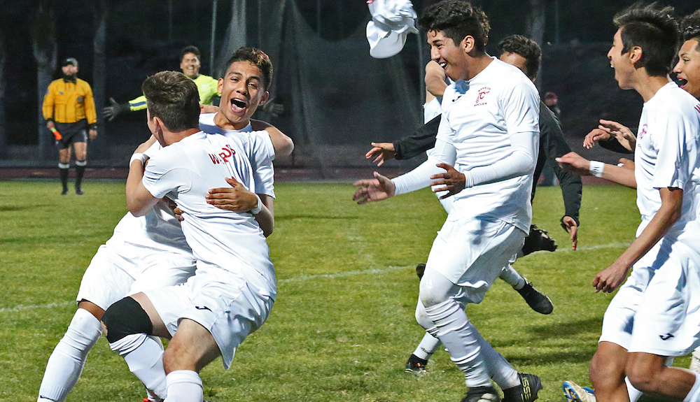 Carpinteria players rush Jose Jimenez after he converts the deciding shot in a penalty-kick shootout in the SoCal Regional semifinals.