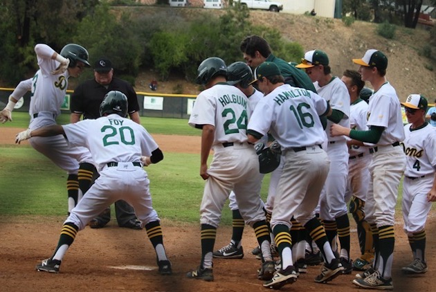 Zach Jensen leaps to home plate as his Santa Barbara teammates wait to mob him after his go-ahead, three-run homer in the fourth inning.