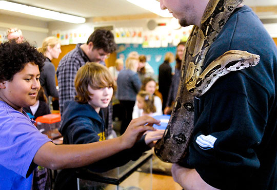 Hollister School students check out a Colombian red-tailed boa.