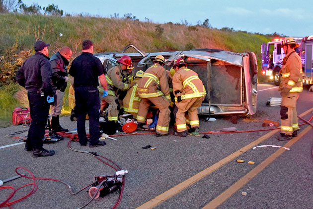 Santa Barbara County firefighters work to extricate a driver who was trapped in the wreckage of a pickup that overturned early Sunday on Highway 154 near Santa Barbara.