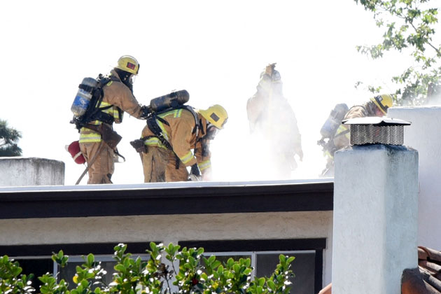 Santa Barbara County firefighters ventilate the roof of a four-plex near More Mesa that caught fire Monday. Two units were left uninhabitable for the blaze.
