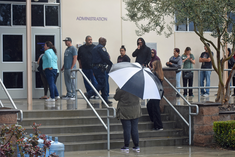 With rain falling parents wait to check their students out of Righetti High School in Orcutt after a lockdown on Wednesday