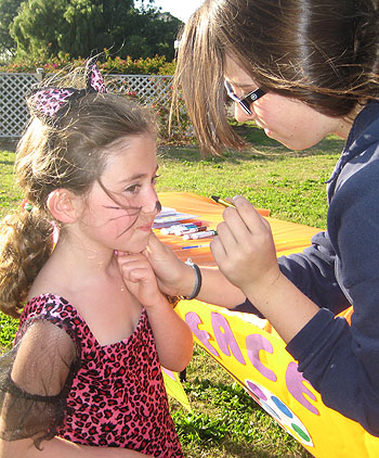 Rachel Rabinowitz gets her whiskers touched-up by face painter Rochel Holden.